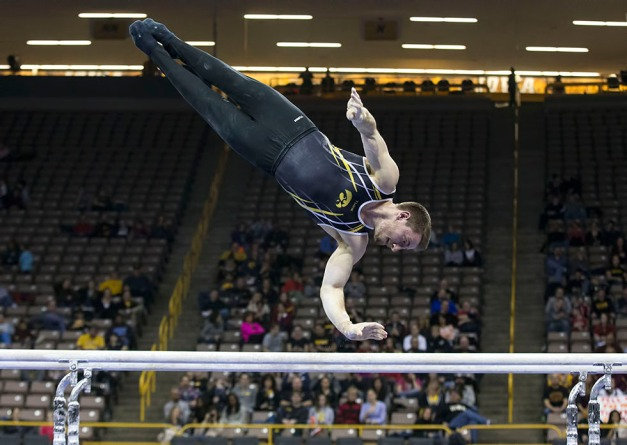 Iowa's Jack Boyle competes on the parallel bars during their meet against Minnesota and Nebraska Saturday, Jan. 24, 2015 at Carver-Hawkeye Arena.  (Brian Ray/hawkeyesports.com)
