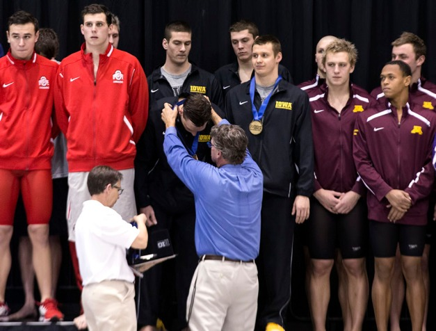 The Hawkeye 200 Medley Relay team is presented with the medals during the first session of the 2015 Big Ten Men's Swimming and Diving Championships Wednesday, Feb. 25, 2015 at the Campus Recreation and Wellness Center on the University of Iowa campus in Iowa City, Iowa.  (Brian Ray/hawkeyesports.com)