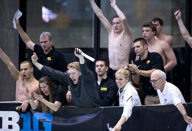 Iowa's associate head coach Frannie Malone, assistant coach Brandon King, assistant coach Kristy Brager, assistant coach Nathan Mundt, and head coach Marc Long cheer on Thomas Rathbun as he swims in the preliminaries of the 200 yard freestyle during the fourth session of the 2015 Big Ten Men's Swimming and Diving Championships Friday, Feb. 27, 2015 at the Campus Recreation and Wellness Center on the University of Iowa campus in Iowa City, Iowa.  (Brian Ray/hawkeyesports.com)