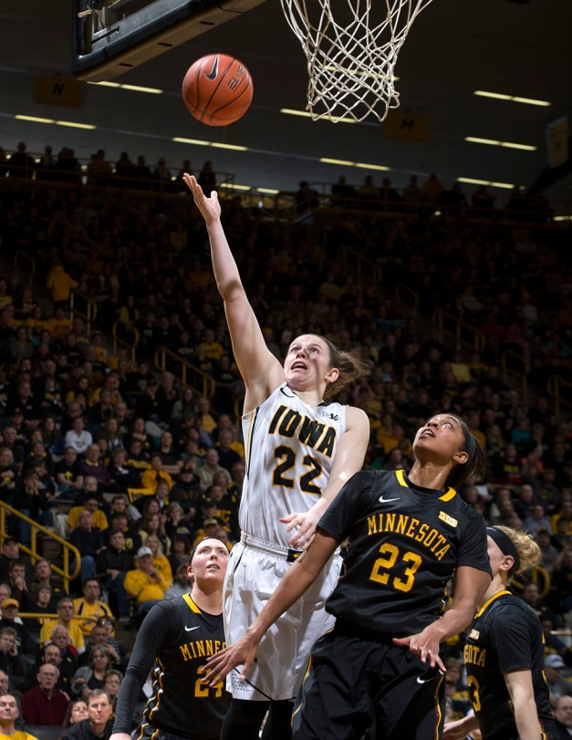 Iowa Hawkeyes guard Samantha Logic (22) goes to the hoop over Minnesota Golden Gophers forward Shae Kelley (23) during the second half of their game Sunday, March 1, 2015 at Carver-Hawkeye Arena.  (Brian Ray/hawkeyesports.com)