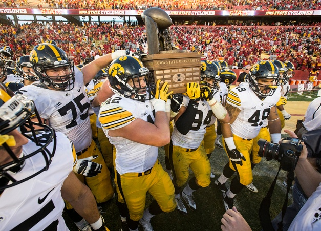 Iowa Hawkeyes fullback Macon Plewa (42) and defensive end Nate Meier (34) carry the Cy-Hawk trophy to the fans following their victory over the Iowa State Cyclones in the Iowa Corn Cy-Hawk Series Saturday, Sept. 12, 2015 at the Jack Trice Stadium in Ames. (Brian Ray/hawkeyesports.com)