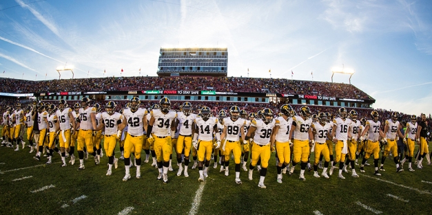 The Iowa Hawkeyes swarm across the field to collect the Cy-Hawk trophy following their victory over the Iowa State Cyclones Wednesday, Sept. 16, 2015 in Ames. (Max Allen/Hawkeye Football)